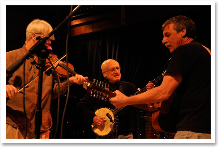 Andy performing at Acorn with Jim Harvey and a fiddle player